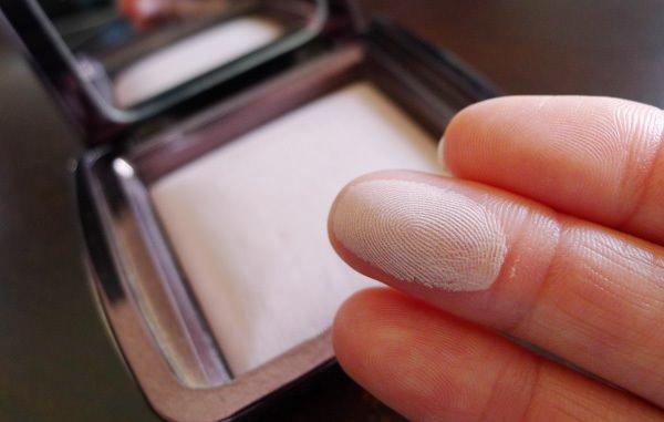 палец с косметикой для лица крупным планом