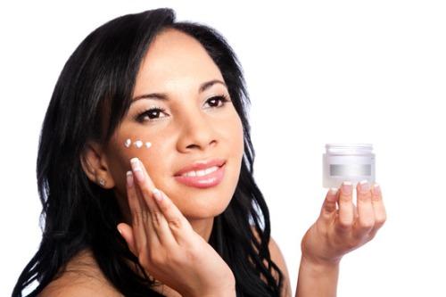 девушка во время нанесения крема на лицо