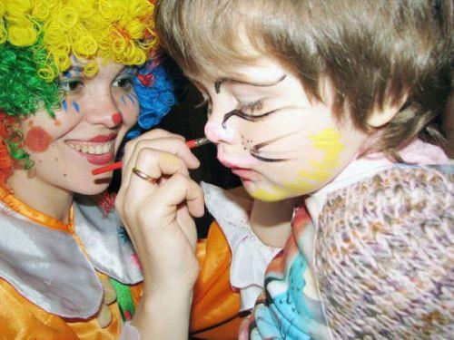 девушка клоун рисует на лице