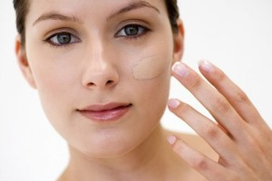 девушка наносит косметику на лицо пальцем