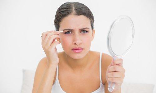 девушка с овальным лицом держит в руке зеркало