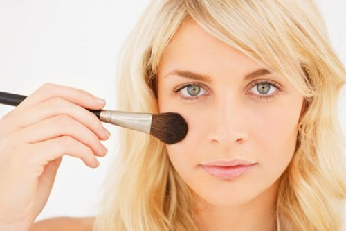 блондинка тонирует лицо кистью для макияжа
