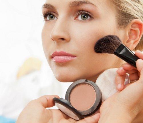 молодой женщине наносят макияж кистью