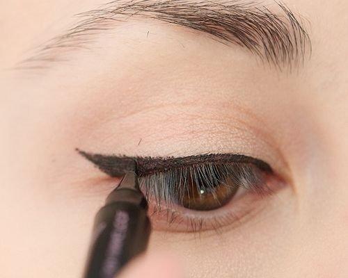 рисует черную стрелку на глазу