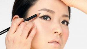 красит карандашом азиатские глаза