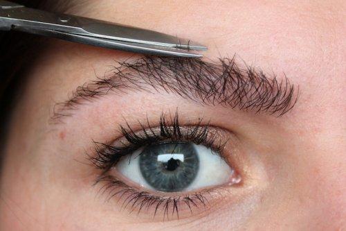 голубоглазая девушка подстригает бровь